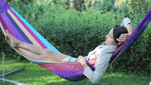 businesswoman swinging in a hammock and drinking beer