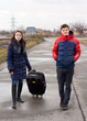 Young couple walking on the road with a suitcase