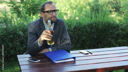 businessman resting after work and drinking beer