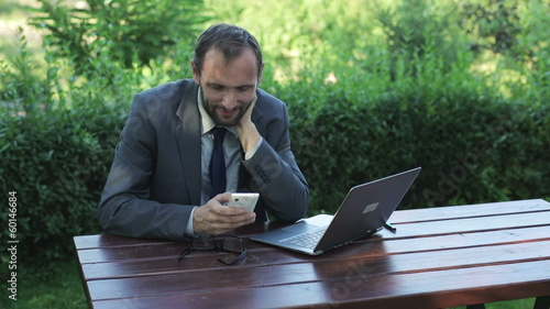 businessman using his smartphone and sitting in the garden