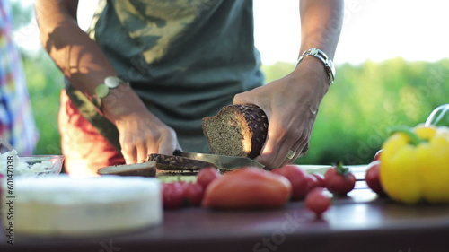 woman's hands cutting bread with a knife