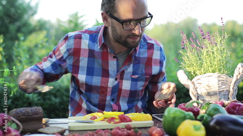 man preparing sandwich by the table in the garden