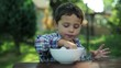 little boy eating soup with fingers by the table in the garden