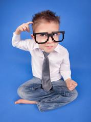 Six years thoughtful boy wearing computer geek glasses