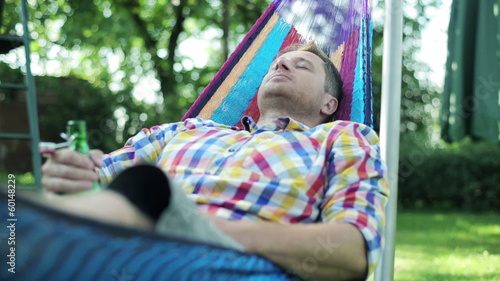 man drinking beer and lying in the hammock