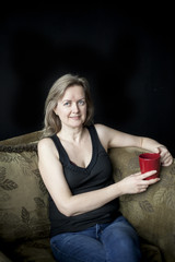 Blonde Woman with Red Coffee Cup on Black Background