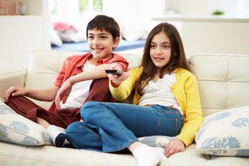 Two Hispanic Children Sitting On Sofa Watching TV Together