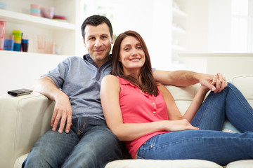 Hispanic Couple Sitting On Sofa Watching TV Together
