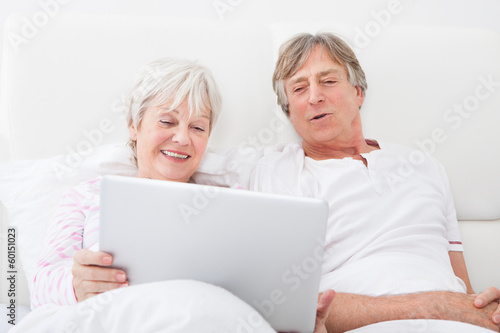 Senior Couple On Bed Looking At Laptop