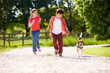 Hispanic Children Taking Dog For Walk In Countryside