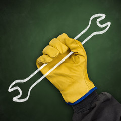 Worker hand with protective glove holding chalk wrench