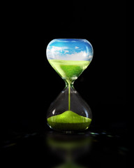 Hourglass with green meadow