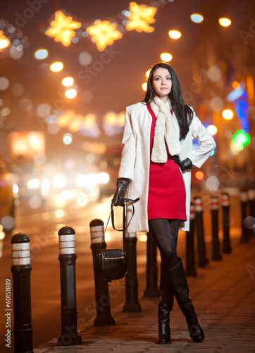 Fashionable lady wearing red dress and white coat outdoor