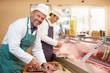 Two Butchers Preparing Meat In Shop