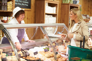 Female Sales Assistant Serving Customer In Delicatessen