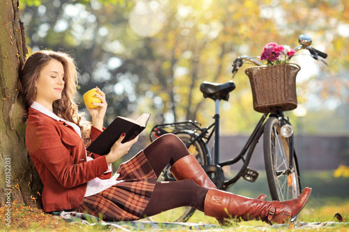 Young female in park reading book and eating apple