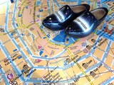 Pair of black Dutch wooden clogs on a map of Amsterdam