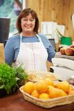 Female Sales Assistant At Checkout Of Farm Shop