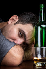 Drunk and depressed man drinking alone