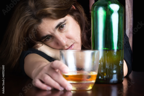 Grunge dark image of a drunk and depressed lonely woman