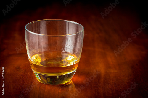 Glass of scotch or rum on a vintage wooden table