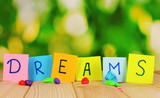 "The word ""Dreams"" on wooden table on natural background"