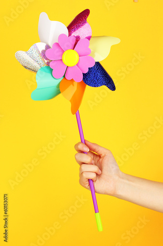Colored pinwheel in hand on yellow background