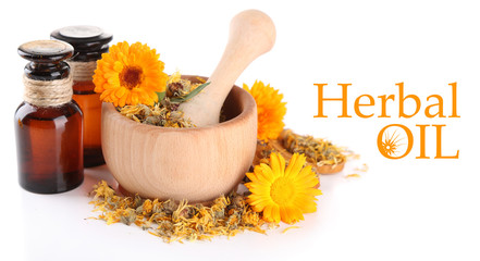 Medicine bottles and calendula flowers in wooden mortar