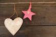 Decorative heart and star on rope, on grey wooden background