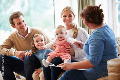 Leinwandbild Motiv Health Visitor Talking To Family With Young Baby