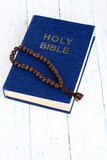 Bible with cross on wooden table close-up