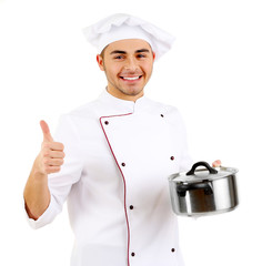 Professional chef in white uniform and hat, holding pan in his