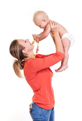 Young Caucasian woman playing with her baby son over white