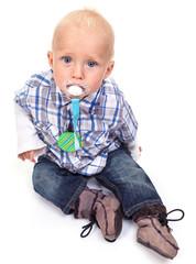 Closeup of cute blonde blue-eyed little boy with a pacifier