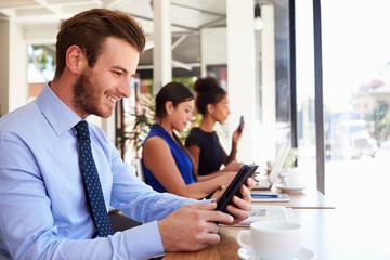 Businessman Using Digital Tablet In Coffee Shop
