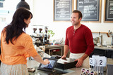 Customer Paying In Coffee Shop Using Touchscreen