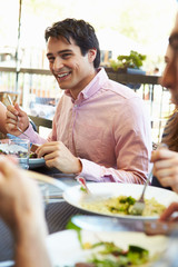 Man Enjoying Meal At Outdoor Restaurant With Friends