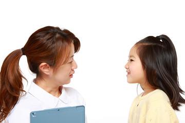 子供の患者に話しかける日本人ナース