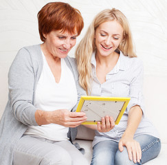 Mother with daughter looking at photo frame