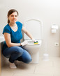 Smiling  woman cleaning toilet seat