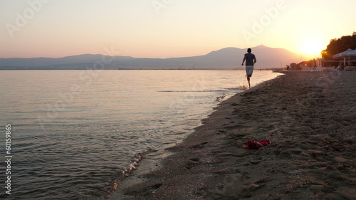 Man running along a beach at sunset