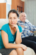 Sad mature woman against husband at home
