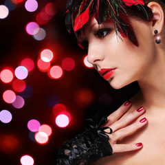 Fashion girl with feathers. Glamour young woman with red lipstic