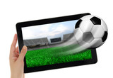 Hand holding tablet with soccer ball flying off screen