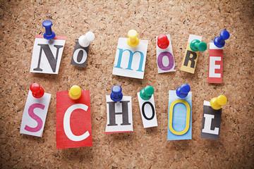 """Message """"NO MORE SCHOOL"""" on cork board ."""