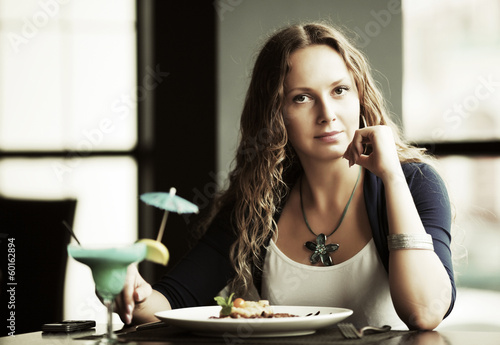 Beautiful young woman dining at restaurant