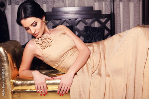 beautiful brunette in beige dress lying on divan