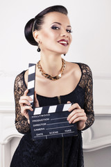 beautiful smiling girl with cinema clapperboard