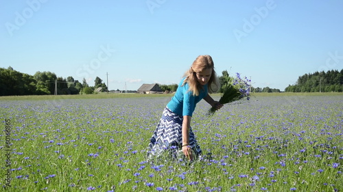 turn view of elegant lady pick bunch of blue cornflower flowers