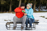 young man and woman sitting on a sledge and sharing a cup of hot poster